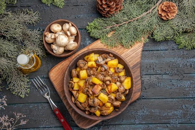 Draufsichtteller an bord teller mit kartoffelpilzen auf holzbrett neben der gabel unter einer schüssel mit pilzöl in flasche und ästen mit zapfen