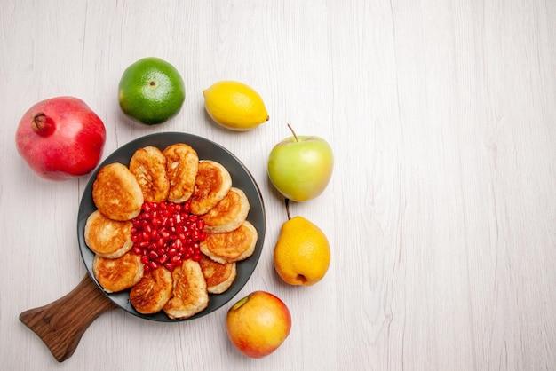 Draufsichtteller an bord teller mit pfannkuchen und granatapfel auf dem holzbrett und granatapfel apfel birne zitrone und limette drum herum auf dem tisch