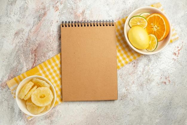 Draufsichtteller auf dem cremefarbenen notizbuch der tischdecke und teller mit getrockneten ananas und zitrusfrüchten auf der karierten tischdecke