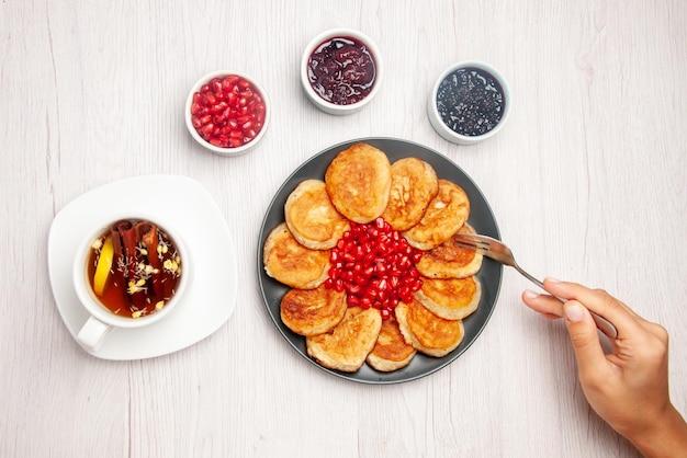 Draufsichtteller auf dem weißen tisch schüsseln mit marmeladenteller mit pfannkuchengabel in der hand und eine tasse kräutertee mit zitrone auf dem tisch