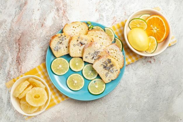 Draufsichtteller auf der tischdecke blauer kuchen- und limettenteller neben den schalen mit getrockneten ananas und zitrusfrüchten auf der karierten tischdecke