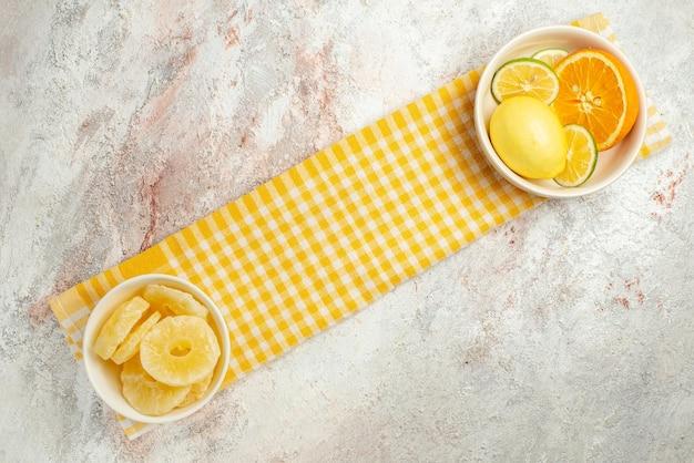 Draufsichtteller auf der tischdecke teller mit getrockneten ananas und zitrusfrüchten auf der karierten tischdecke
