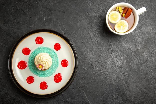 Draufsichtteller mit cupcake eine tasse tee mit zitronen- und zimtstangen und einen teller mit appetitlichem cupcake auf dunklem hintergrund