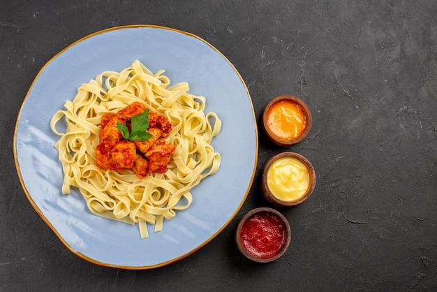 Draufsichtteller mit soßen appetitliche nudeln mit soße und fleisch auf dem teller neben den drei soßen auf dem dunklen tisch
