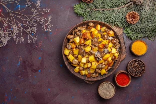 Draufsichtteller mit speiseteller mit bratkartoffeln und pilzen verschiedene gewürze neben den tannenzweigen mit zapfen