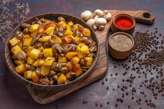 Draufsichtteller mit speiseteller mit kartoffeln mit champignons, weißen champignons und bunten gewürzen