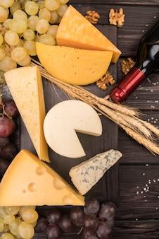 Draufsichtvielzahl des geschmackvollen käses mit trauben auf dem tisch