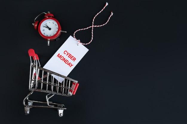 Draufsichtwecker und warenkorb mit cybermontag-aufkleber auf einem schwarzen. zeitmanagement, online-shopping.