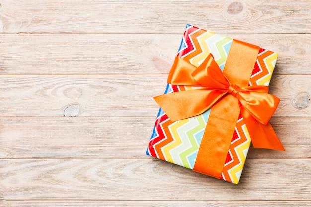 Draufsichtweihnachten oder anderes handgemachtes präsentkartonpaket des feiertags, gelbes hölzernes copyspace der ebenenlage. geschenkbox