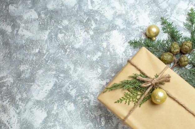 Draufsichtweihnachtsgeschenk mit grünem zweig auf weißem weihnachtsfarbfeiertagsfotogeschenk neues jahr