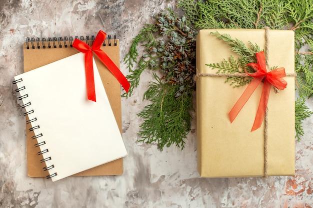 Draufsichtweihnachtsgeschenk mit grünem zweig auf weißer urlaubsgeschenkfarbe neues jahr xmas