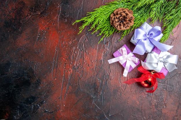 Draufsichtweihnachtsgeschenke baumzweige mit kegelweihnachtsbaumspielzeug auf dunkelrotem hintergrund
