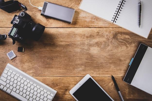 Draufsichtweinleseart des fotografen, der aus kameras, einer tastatur, einem intelligenten telefon besteht