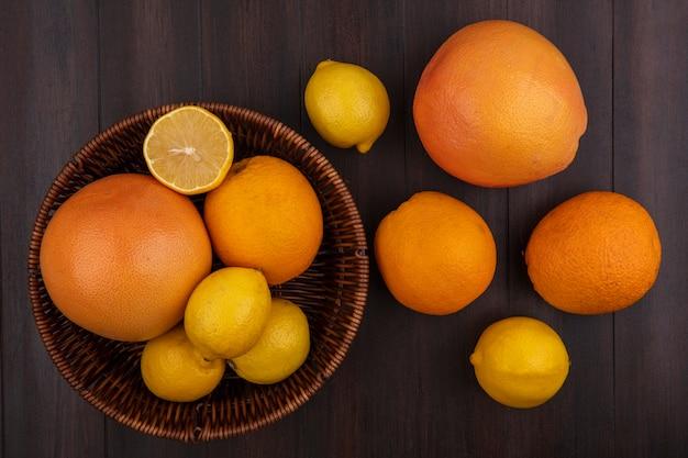 Draufsichtzitronen mit orangen und grapefruits mit korb auf hölzernem hintergrund