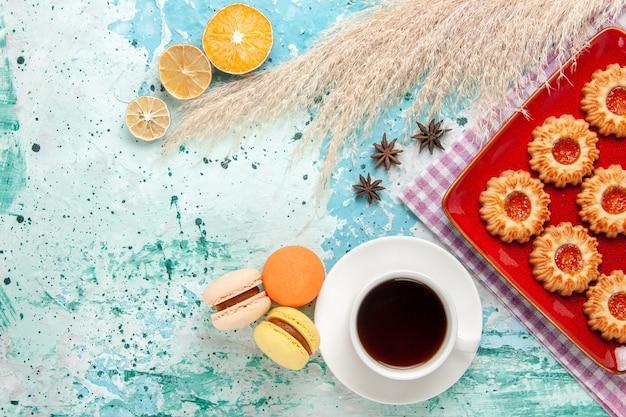 Draufsichtzuckerplätzchen innerhalb der roten platte mit tasse tee und macarons auf dem blauen hintergrund