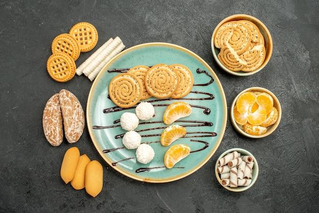 Draufsichtzuckerplätzchen mit bonbons und keksen auf grauem hintergrund