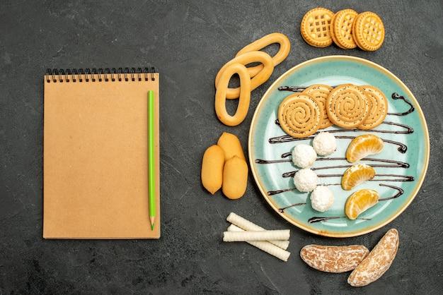 Draufsichtzuckerplätzchen mit keksen und bonbons auf dem grauen hintergrund