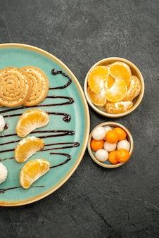 Draufsichtzuckerplätzchen mit mandarinenbonbons auf grauem hintergrund