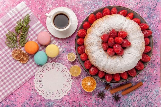 Draufsichtzuckerpulver-erdbeerkuchen der draufsicht mit französischen macarons auf rosa