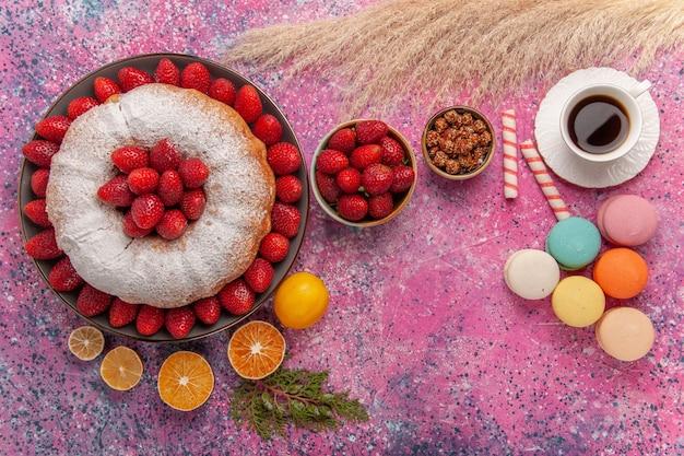 Draufsichtzuckerpulver-erdbeerkuchen der draufsicht mit tee und macarons auf rosa