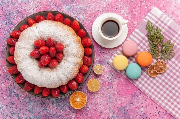 Draufsichtzuckerpulver-erdbeerkuchen mit macarons auf dem rosa