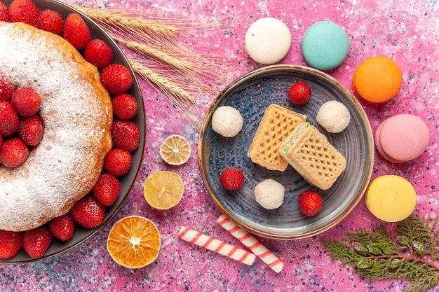 Draufsichtzuckerpulver-erdbeerkuchen mit waffeln und macarons auf rosa