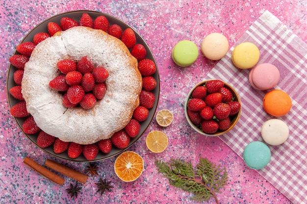 Draufsichtzuckerpulverkuchen mit französischen macarons auf rosa
