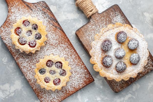 Draufsichtzuckerpulverkuchen mit früchten auf der grauen schreibtischkuchenkekszuckersüßfrucht