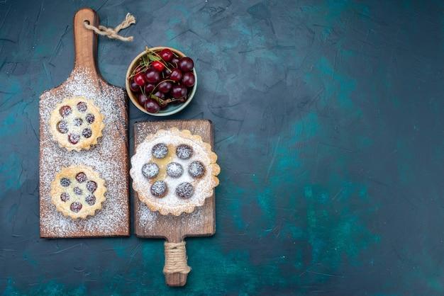 Draufsichtzuckerpulverkuchen mit frutis zusammen mit frischen früchten auf dem dunklen hintergrundfruchtkuchen-keks süßes backen