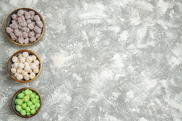 Draufsichtzuckersüßigkeiten in kleinen tellern auf einem weißen hintergrundzuckerzuckerbonbon süßer keks