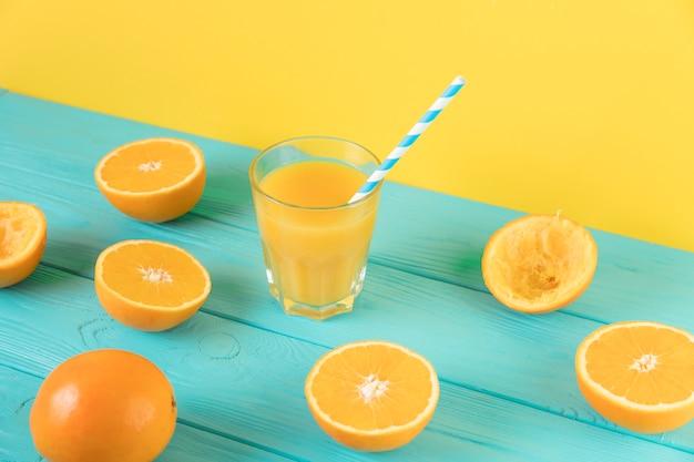 Draufsichtzusammensetzung des frischen orangensaftes auf blauer tabelle
