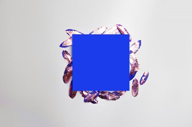 Draufsichtzusammensetzung des rahmens des blauen papiers mit gold verlässt auf einem grau