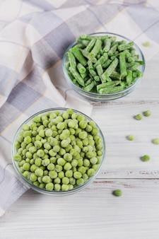 Draufsichtzusammensetzung mit verschiedenen organischen gefrorenem gemüse auf weißer holzoberfläche. grüne bohnen und erbsen in einer schüssel