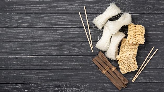 Draufsichtzusammenstellung von ungekochten nudeln und von essstäbchen mit kopienraum