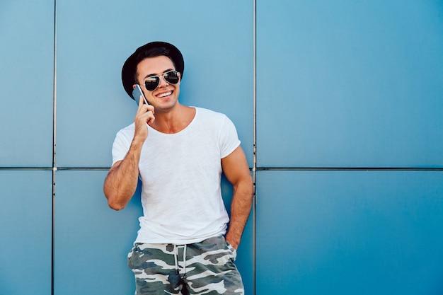 Draußen foto des frohen stilvollen jungen mannes, der mit smartphone, tragender schwarzer hut benennt