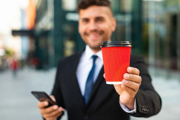 Draußen geschäftsmann, der eine rote tasse kaffee hält