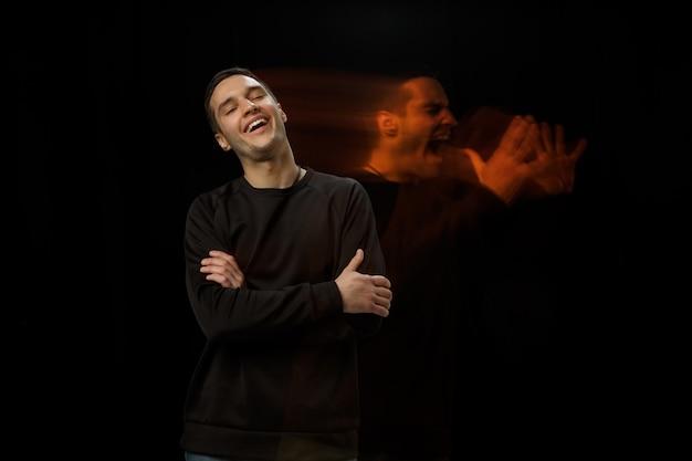 Draußen lachen, drinnen schreien. die vielseitigkeit des menschen - geöffnete emotionen und verborgene gefühle. kaukasischer mann auf schwarzer wand mit verschiedenen gesichtern des zustands. doppelbelichtung. psychische gesundheit.