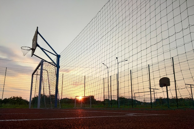 Draußen minifußball- und basketballplatz mit dem balltor und -korb umgeben mit hohem schutzzaun.