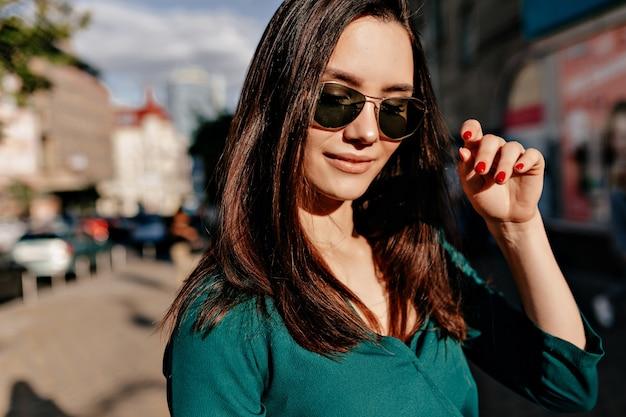 Draußen nahaufnahmeporträt der bezaubernden europäischen frau, die schwarze sonnenbrille und grüne bluse aufwirfend aufwirft