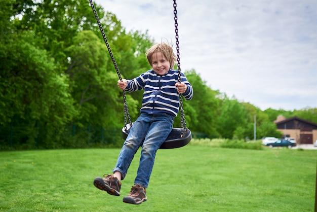 Draußen porträt des niedlichen lachenden jungen der vorschule, der auf einer schaukel am spielplatz schwingt