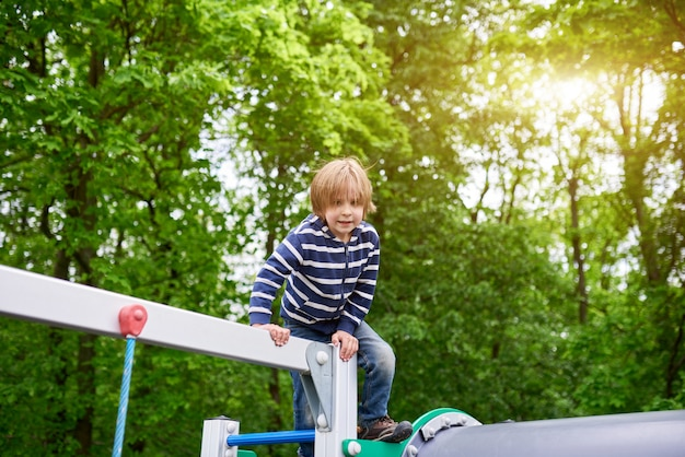 Draußen porträt des niedlichen vorschuljungen, der am spielplatz klettert