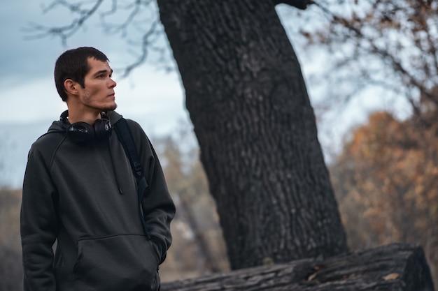 Draußen porträt eines hübschen bärtigen mannes, der ein mit kapuze sweatshirt in einem park trägt