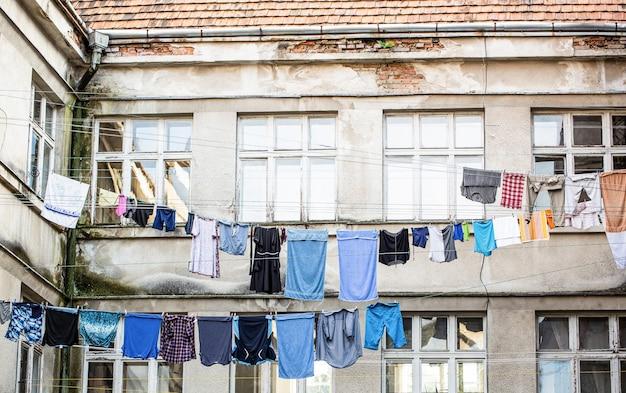 Draußen trocknen frische, saubere kleidung. kleidung zum trocknen an einer wäscheleine hängen. wäschetrocknung am seil. gewaschene kleidung, die außerhalb eines alten hauses trocknet. gewaschene wäsche trocknen.