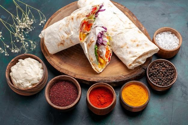 Draußenansicht köstliches fleischsandwich aus fleisch, das auf einem mit gewürzen geschnittenen spieß auf dem blauen schreibtisch gegrillt wird