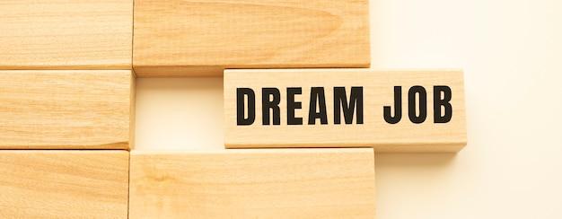 Dream job-text auf einem holzstreifen, der auf einem weißen tisch liegt.