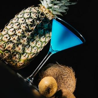 Drehen sie ansicht des cocktails und der exotischen früchte auf schwarzem hintergrund