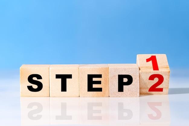 Drehen sie den holzwürfel mit dem wort schritt 1 bis schritt 2 auf dem blauen tisch. unternehmenskonzept