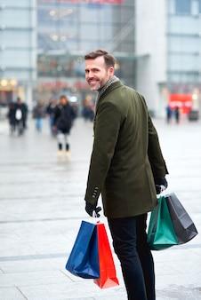 Drehender mann mit einkaufstüten, die die stadtstraße entlang gehen