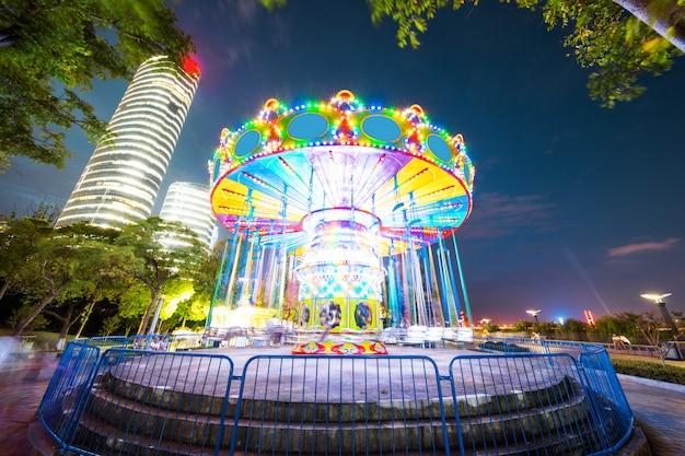 Drehendes belichtetes anziehungskraft-riesenrad und karussell-karussell am sommer-abend im stadt-vergnügungspark.