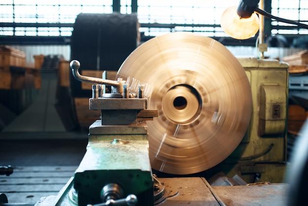 Drehmaschine in bewegung auf metallbearbeitungsfabrik, niemand. metallherstellung, metallarbeiten, die anlage einschalten. turner arbeitsplatz, werkzeuge und geräte für die stahlverarbeitung